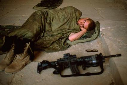 The soldier lay sleeping, silent, alone, curled up on the floor in ...